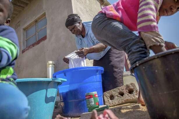Sikhathele Ndlovu does laundry with the help of her two grandchildren in Cowdray Park, Bulawayo, Zimbabwe.