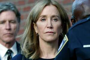 Felicity Huffman leaves federal court with her brother Moore Huffman Jr. following, after she was sentenced in a nationwide college admissions bribery scandal, Friday, Sept. 13, 2019, in Boston. (AP Photo/Michael Dwyer)