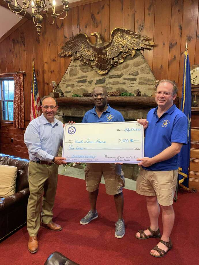 Captain John Carter, USNR, left, accepting the check from Silas Mante, Master of Ivanhoe Lodge#107 A.F. & A.M. and David Zecchin, President of the Masonic Club of Darien, Inc. Photo: The Masonic Club Of Darien, Inc.