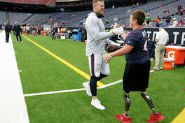 Houston Texans defensive end J.J. Watt greets Calder Hodge as he plays catch with fans before an NFL football game against the Jacksonville Jaguars at NRG Stadium on Sunday, Sept. 15, 2019, in Houston.