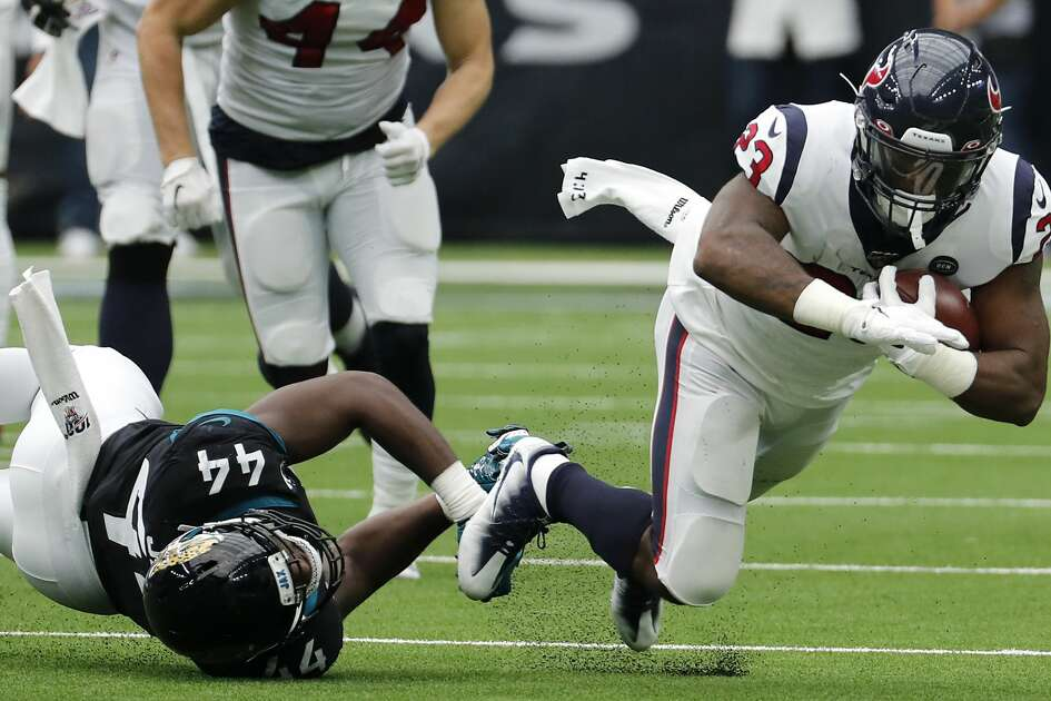 Houston Texans running back Carlos Hyde (23) is tripped up by Jacksonville Jaguars middle linebacker Myles Jack (44) during an NFL football game at NRG Stadium on Sunday, Sept. 15, 2019, in Houston.
