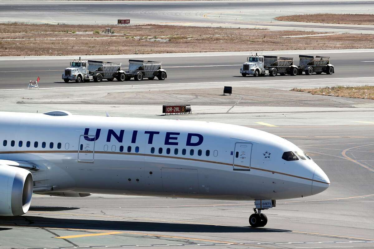 Construction trucks drive past a United plane at SFO in San Francisco, Calif., on Sunday, September 15, 2019.