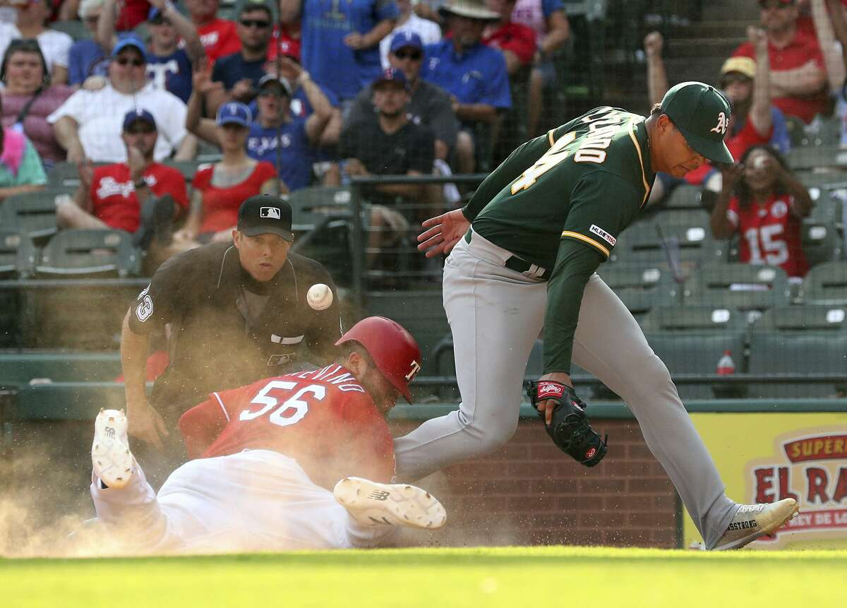 Texas Rangers Jose Trevino (56) scores on a passed ball as Oakland Athletics pitcher Jesus Luzardo (44) tries to guard the plate in the eighth inning in a baseball game Sunday, Sept. 15, 2019, in Arlington, Texas. (AP Photo/Richard W. Rodriguez)
