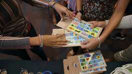 Loteria cards are handed out during the La Lote event at the San Antonio Central Library on Sunday. La Lote featured an afternoon of lotería-inspired art and activities, including interactive readings and lotería games.