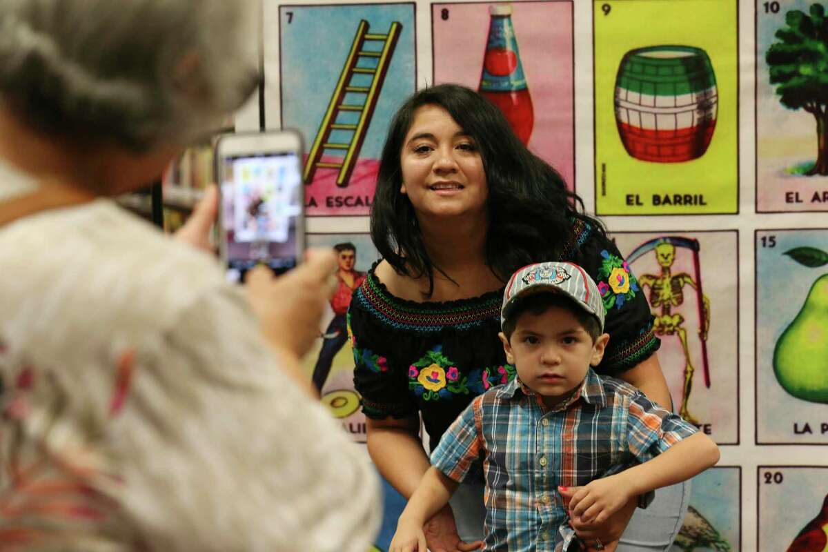 Jeannie Prado poses with her son, Jude Hernandez, 3, in front of an over-sized lotería card during La Lote at the San Antonio Central Library on Sunday. La Lote featured an afternoon of lotería-inspired art and activities, including interactive readings and lotería games.