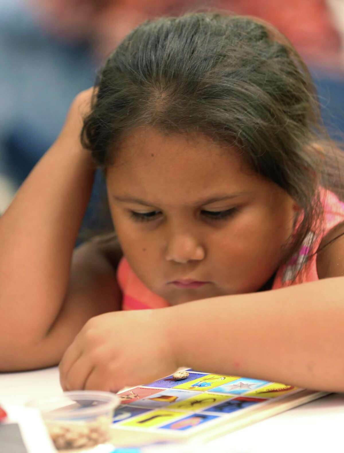 Anastasia Garcia, 6, concentrates on her card during a game of lotería at the San Antonio Central Library on Sunday for the La Lote event.