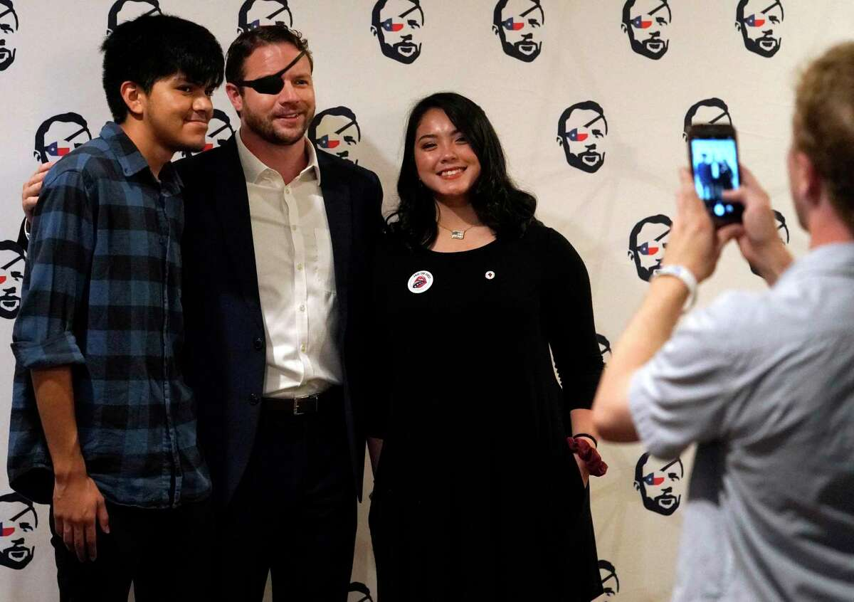 Roman Molina 17, left, and his girlfriend, Madyson Duong, 17, both of Katy, pose for a photo with Congressman Dan Crenshaw during his Youth Summit held at the Hyatt Regency Houston, 1200 Louisiana St., Sunday, Sept. 15, 2019, in Houston. The event was for high school and college students.