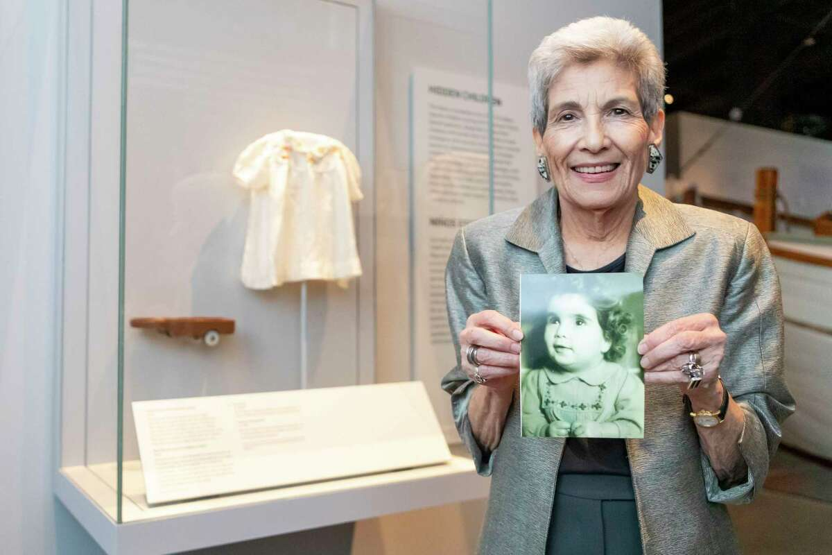 Holocaust survivor Chaja Verveer of Houston, is shown next her toddler gown that is on display at the Holocaust Museum Houston Sunday, Sep 15, 2019, in Houston.