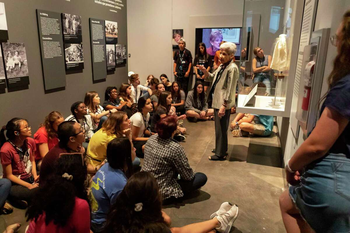 Holocaust survivor Chaja Verveer of Houston, stands next her toddler gown while speaking to local students apart of the Engines of Change student ambassador program at the Holocaust Museum Houston Sunday, Sep 15, 2019, in Houston.