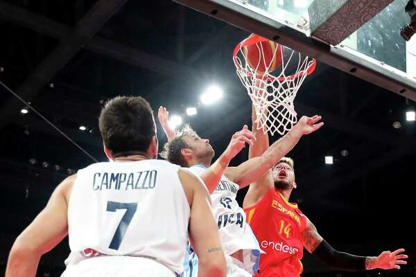 Spain's Willy Hernangomez Geuer, right, tries to dunk near Argentina's Marcos Delia and Facundo Campazzo, left, during the final of the FIBA Basketball World Cup held at the Cadillac Arena in Beijing, Sunday, Sept. 15, 2019. (AP Photo/Ng Han Guan, Pool)