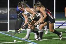 New Canaan's Marlee Smith and Darien's Lindsey Olson battle for the ball during the 2018 CIAC Class L field hockey playoffs at Darien High School.