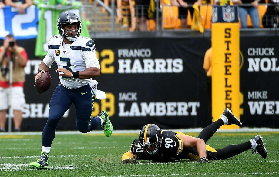 Seahawks QB Russell Wilson scrambles out of the pocket against T.J. Watt of the Steelers in Pittsburgh. Photo: Justin Berl / TNS