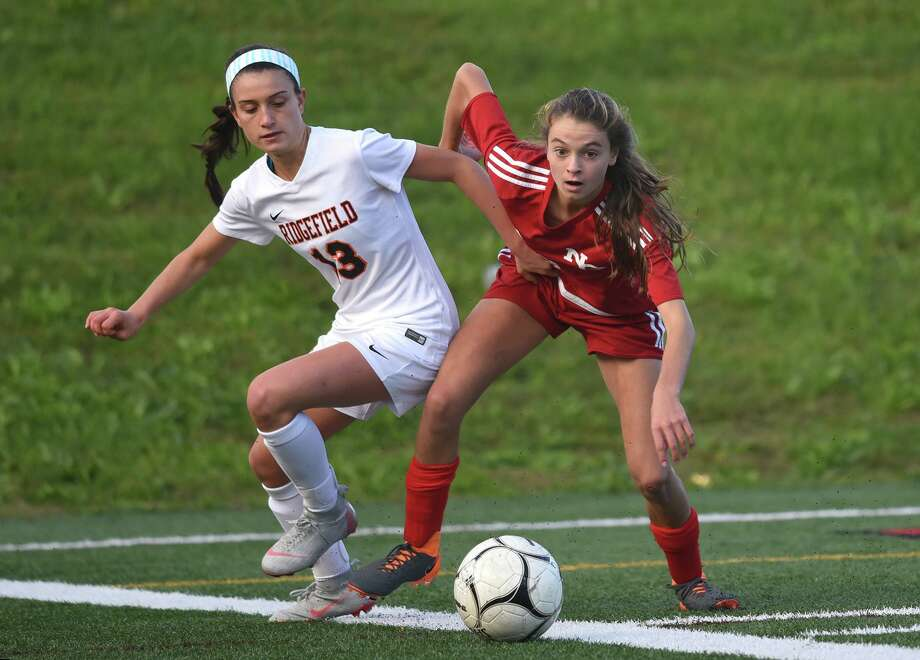 New Canaan's Dillyn Patten, right, and Ridgefield's Amelia Hynes (13) battle for the ball during the Rams' 1-0 win at Dunning Field on Saturday, Oct. 13, 2018. Photo: Dave Stewart / Hearst Connecticut Media / Hearst Connecticut Media