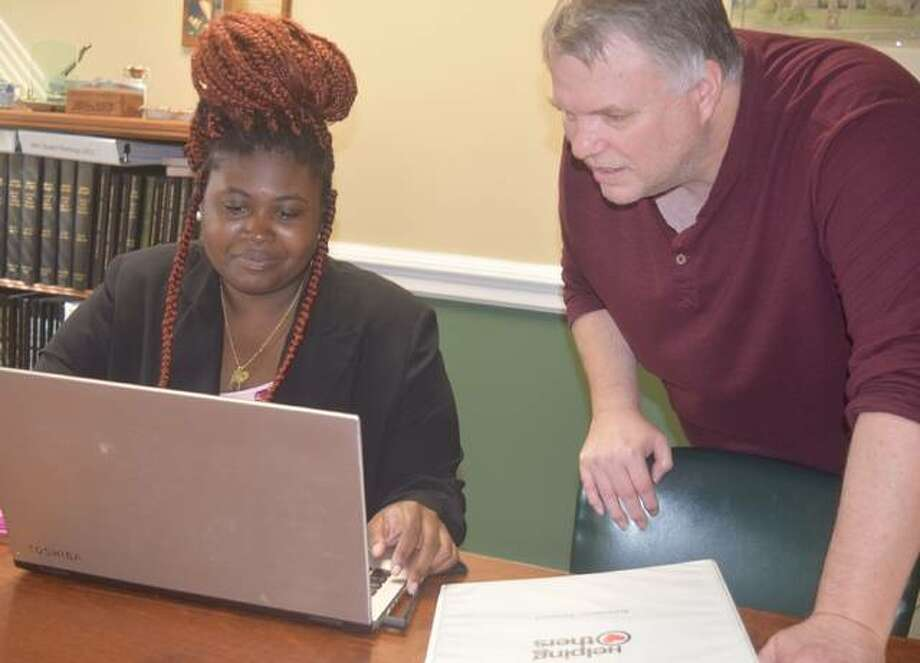 MacMurray College senior Rickayla Wilson (left) and library director Chris Ashmore discuss the social worker internship Wilson is completing at the library this semester. Photo: Samantha McDaniel-Ogletree | Journal-Courier