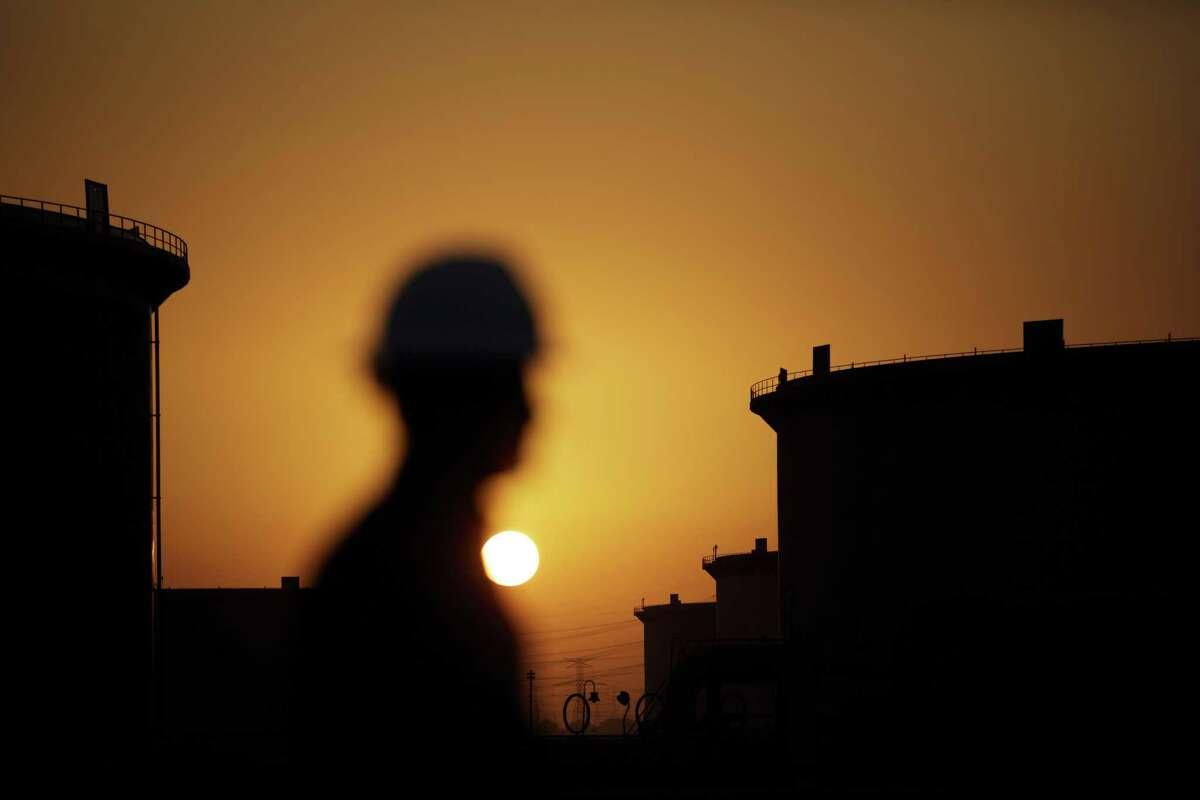 The sun sets over crude oil storage tanks at the Juaymah tank farm, operated by Saudi Aramco, in Ras Tanura, Saudi Arabia, on Oct. 1, 2018.