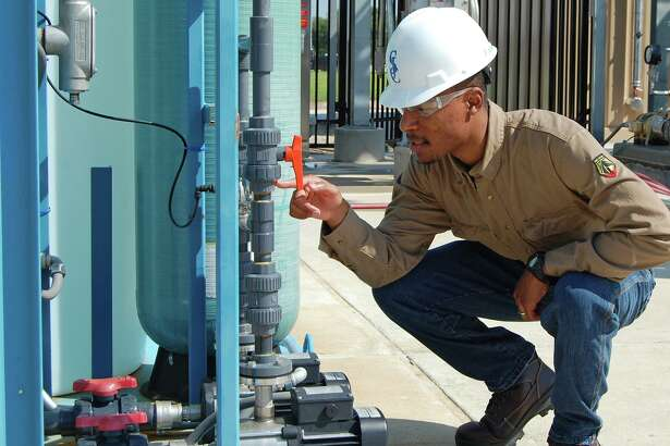 San Jacinto College student Gabriel McKenzie checks a gauge reading on the glycol unit at the new Center for Petrochemical, Energy, and Technology.