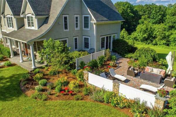 This house has a new stone patio surrounded by new plantings and provides attractive views of the wooded conservation area.