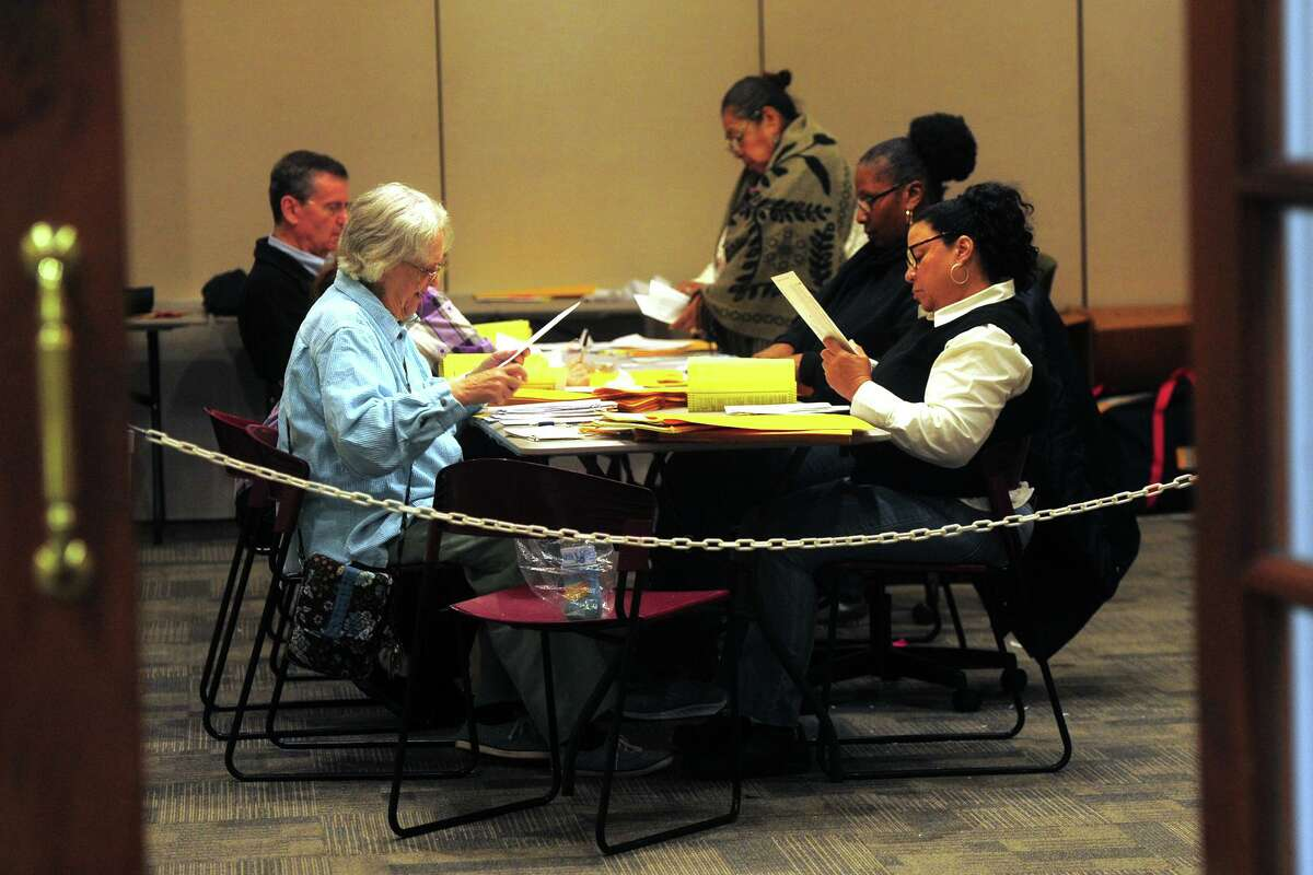 Registrars count absentee ballots on election night at the Morton Government Center, in Bridgeport, Conn. Nov. 6, 2018.