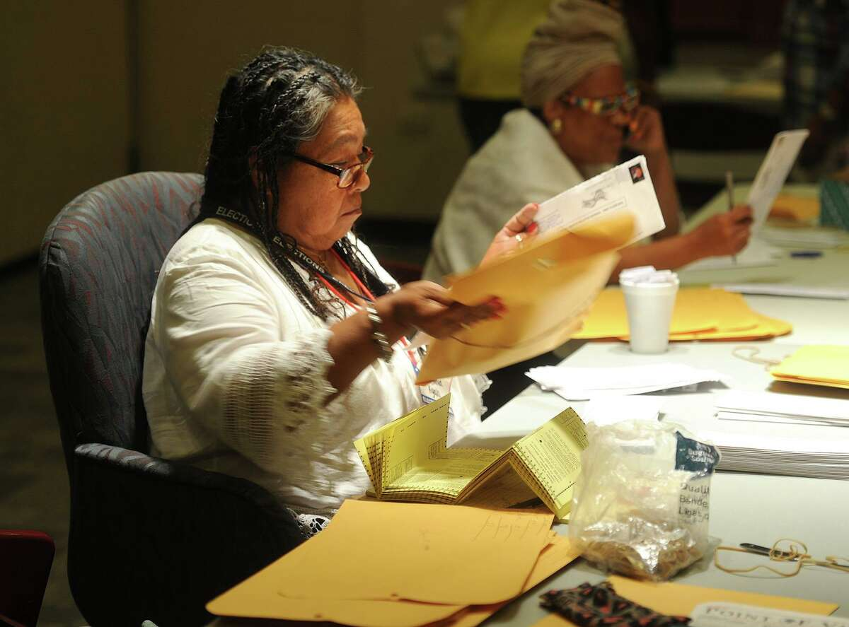 Election official Sonia Ayala, left, sorts Democratic mayoral primary absentee ballots at the Margaret Morton Government Center in Bridgeport on Sept. 16, 2015.