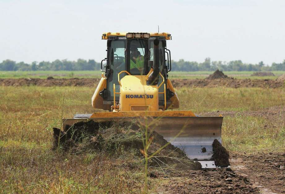 Bulldozers were busy moving dirt in the background during the ceremony that celebrated the groundbreaking for River Ranch, the new master planned community on SH 146 in Dayton. Photo: David Taylor / Staff Photo