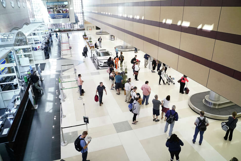Travelers wait to collect their luggage in the baggage claim area of the Albany international airport. Where are some places we wish we could fly to direct from Albany? Click through the slideshow to learn what readers had to say.