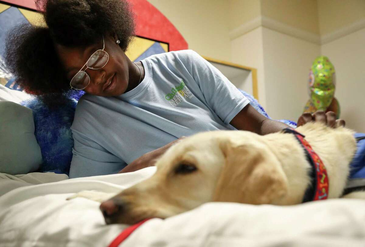 Season Finley, 14, pets Dexter while he naps on her hospital bed at Children's Memorial Hermann Hospital.