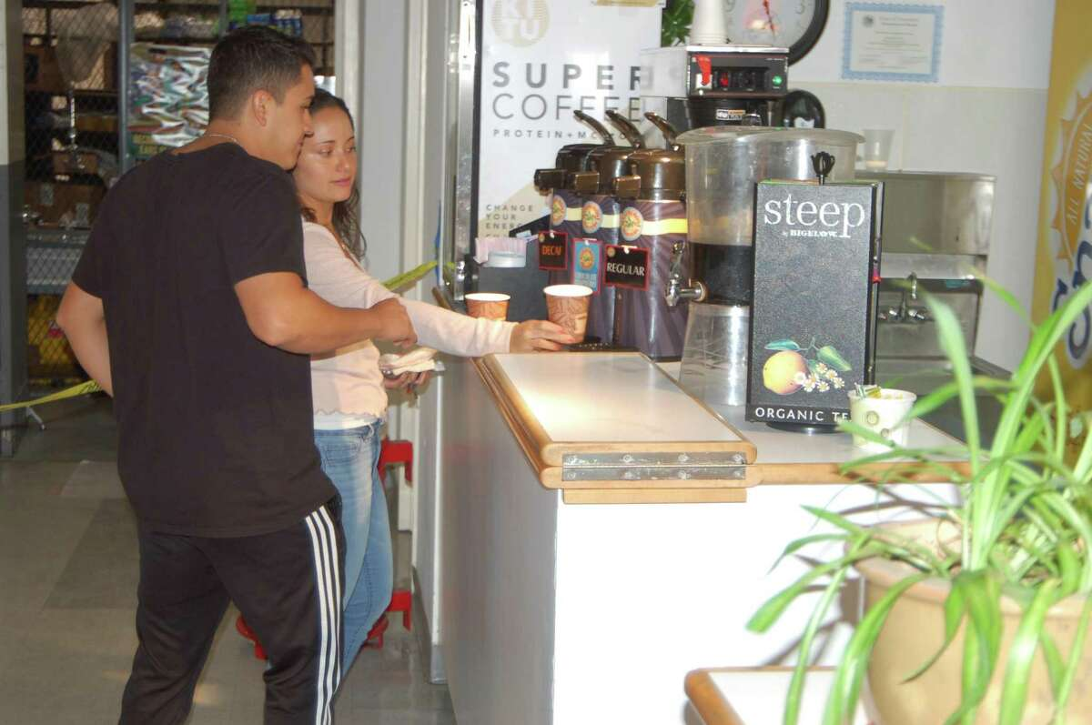 Customers Julieth Alvarez and Juan Jimenez purchase a cup of coffee on Friday at the Greenwich Library café. The future of the cafe is the subject of much discussion as the library begins its renovation project. An online survey is collecting customer in put on food choices, prices and hours for the new cafe.