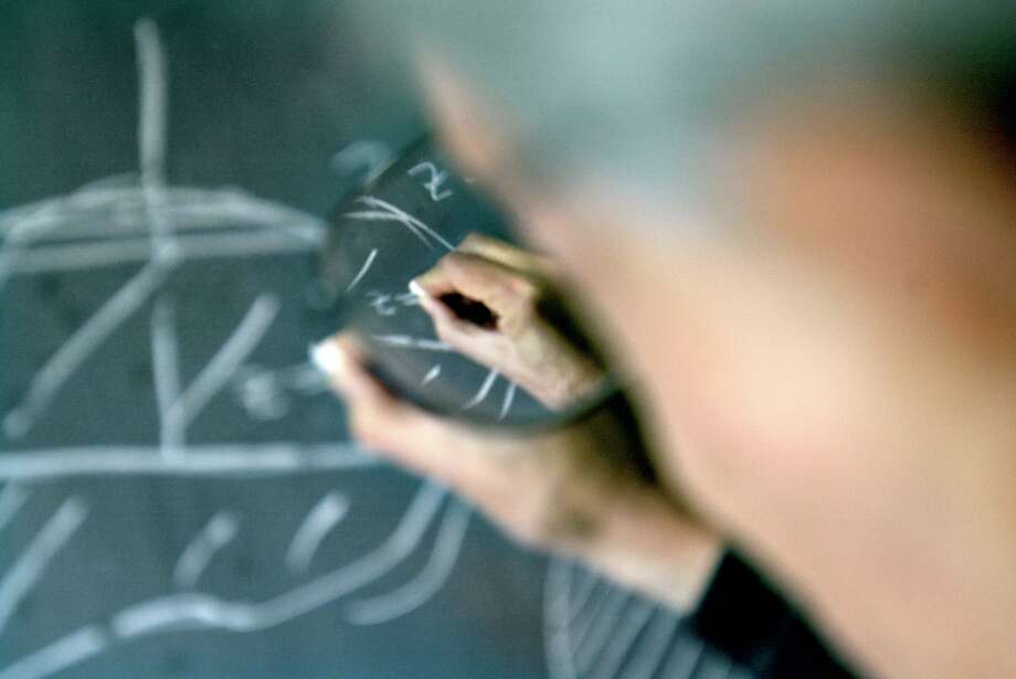 MATH02a-C-26SEP02-DD-CKH CHRISTINA KOCI HERNANDEZ/CHRONICLE Osserman's hand, shot through his glasses, scribbles math problems onto a chalkboard in his office.Robert Osserman, Special Projects Director at the Mathematical Sciences Research Institute. Photo: CHRISTINA KOCI HERNANDEZ / SFC / CHRONICLE