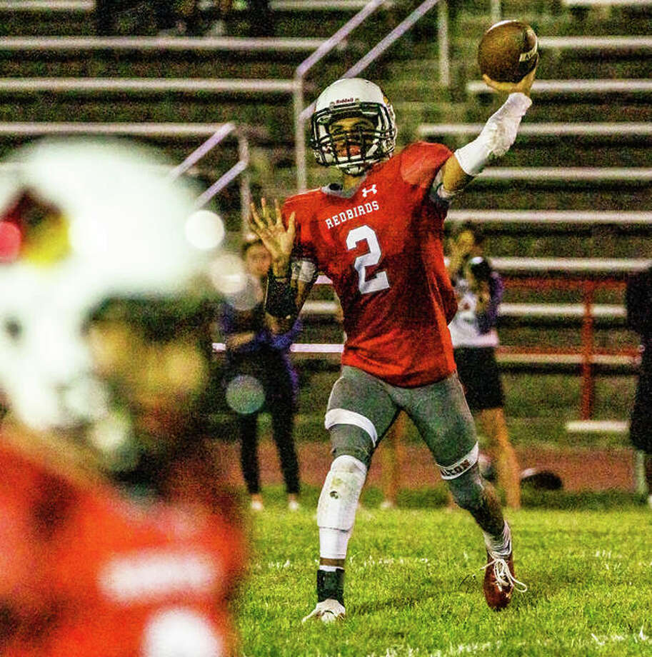 Alton quarterback Andew Jones (2) throws a pass toward the sideline during the Redbirds' 58-6 victory over the Collinsville Kahoks on Friday night at Public School Stadium. Photo: Nathan Woodside / The Telegraph
