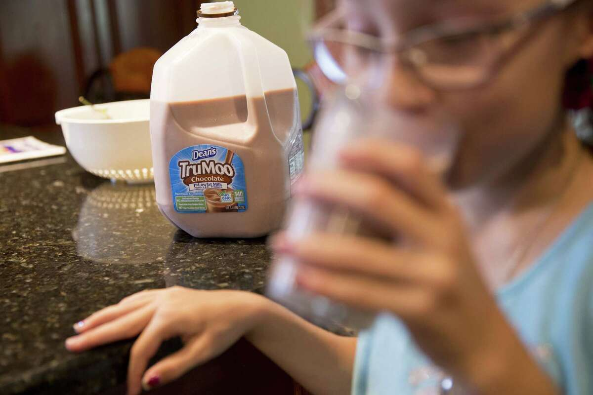 A girl drinks from a glass as a gallon of Dean Foods Co. Dean's TruMoo brand chocolate milk sits on a counter in an arranged photograph in Tiskilwa, Illinois, U.S., on Thursday, Aug. 3, 2017. Dean Foods Co. is scheduled to release earnings figures on August 8. Photographer: Daniel Acker/Bloomberg ORG XMIT: 775020000