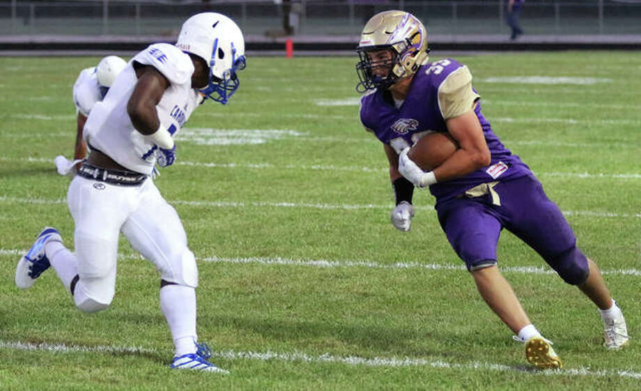 CM running back Nick Walker (right) looks to initiate contact against a Cahokia defender during the first quarter Friday night at Hauser Field in Bethalto. Photo: Greg Shashack / The Telegraph