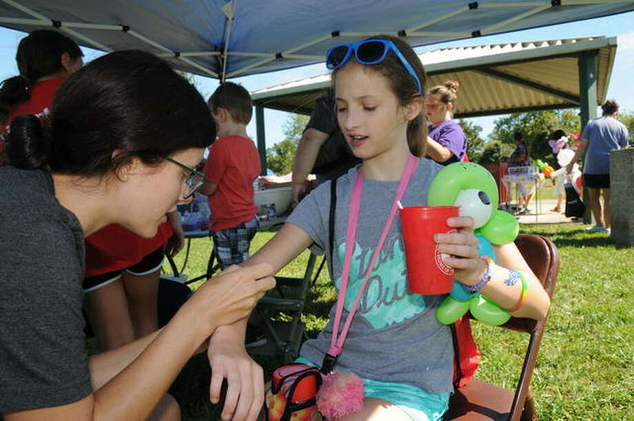 Eleven-year-old Brailey Harrop gets a tattoo during National Day for Kids on Saturday in Bethalto.