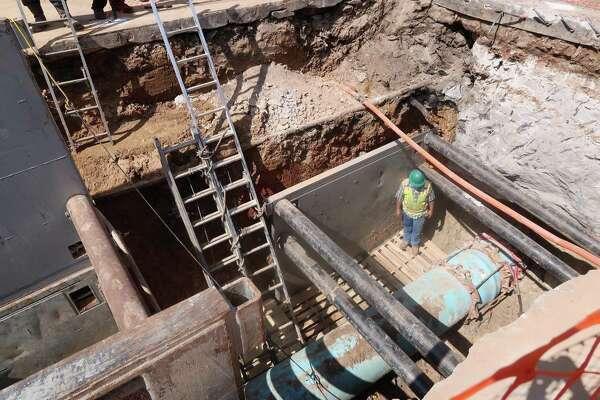 Crews work to inspect a water main that ruptured along Research Forest Drive Friday
