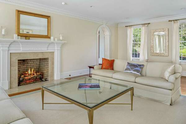 There are six fireplaces in this house, the first is found in the formal living room, which also has French doors to the sitting room or solarium.