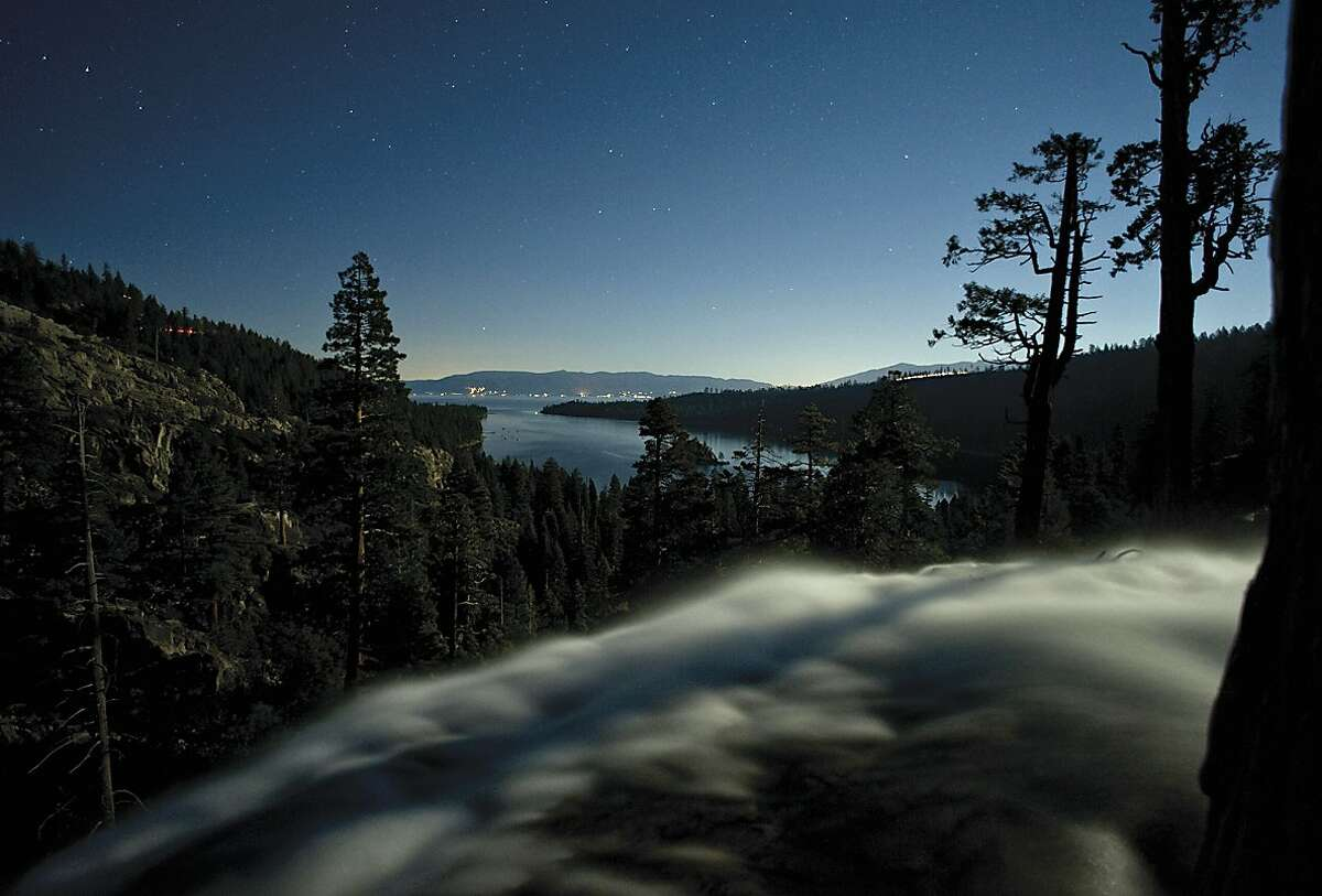 In a time-lapse photo, the rush of the Eagle Falls Cascade is lit in moonlight and backed by Emerald Bay and Lake Tahoe