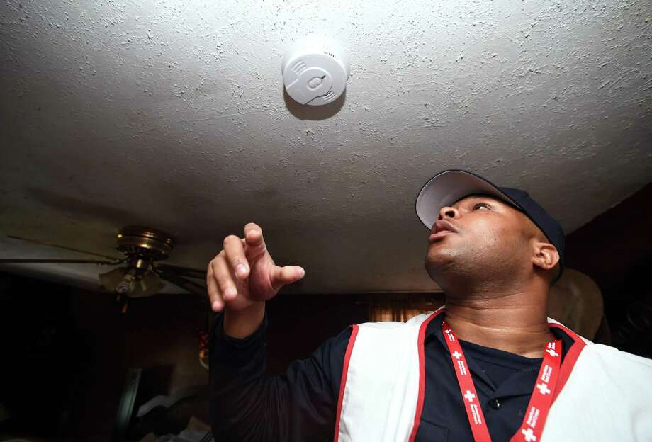 Matthew Watkins installs one of three free smoke alarms at the home of Kelvin Nix in New Haven on April 28, 2018. Around 300 free smoke alarms were installed in New Haven homes during the Red Cross Sound the Alarm event in a collaboration between the American Red Cross and the New Haven Fire Department. Photo: Arnold Gold / Hearst Connecticut Media / New Haven Register