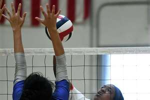 Atascocita senior outside hitter Zaire Miles (13) works at the net against Cy Creek middle blocker Kat Betancourt (8) during their CCISD Varsity Volleyball Tournament Copper Bracket matchup at Clear Brook High School on August 31, 2019.