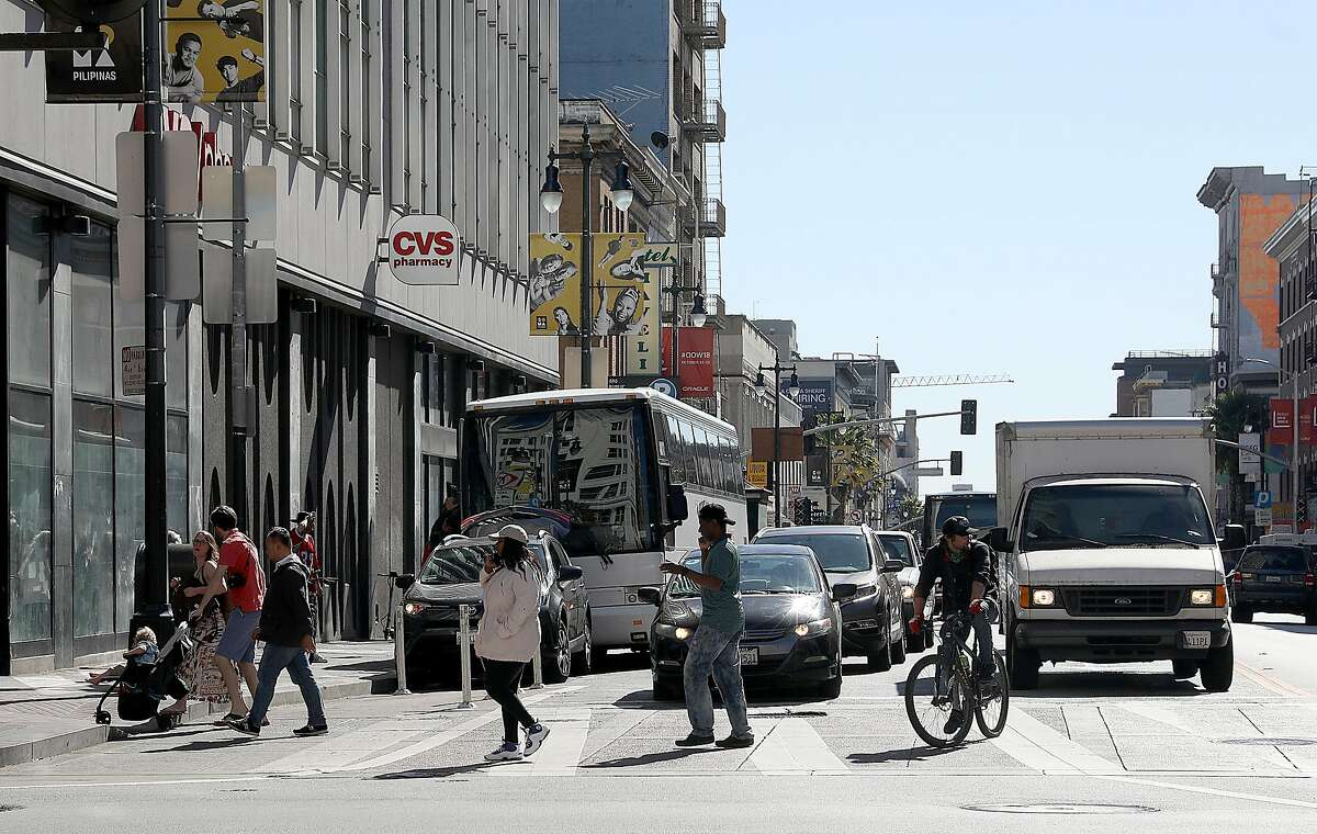 Pedestrians cross on 6th Street at Market Street looking south on Monday, Oct. 15, 2018, in San Francisco, Calif. The SFMTA Board will vote Tuesday on a plan to remove one southbound traffic lane from Sixth Street, a measure to boost safety on a roadway where a pedestrian gets hit by a car about every 16 days.