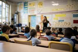 TOPSHOT - Children listen to their teacher as they sit in a classroom on the first day of the start of the school year, at the Chaptal elementary school in Paris, on September 2, 2019. - In France some 12.4 million students crossed the doors of elementary schools (6.7 million), secondary school (3.4 million) and high schools (2.3 million) on September 2, 2019. (Photo by Martin BUREAU / AFP) (Photo credit should read MARTIN BUREAU/AFP/Getty Images)
