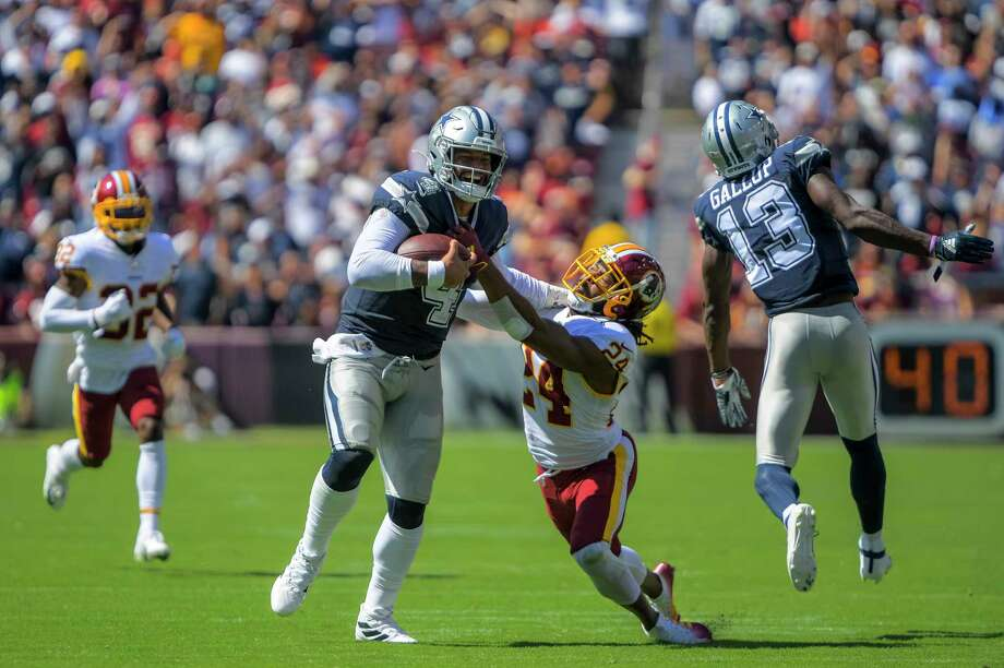 Dallas quarterback Dak Prescott is brought down by Washington cornerback Josh Norman in the second quarter at FedEx Field in Landover, Maryland, on Sunday, Sept. 15, 2019. The Cowboys defeated the Redskins, 31-21. Photo: Washington Post Photo By John McDonnell. / The Washington Post