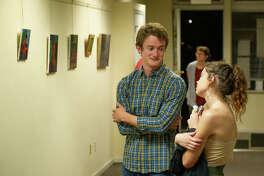 SIUE senior Sutton Allen visits with an attendee during his exhibit at the Youth Education and Health in Soulard. His paintings are displayed in the background.
