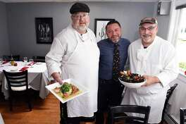 Rosso Vino Wine Bar + Bistro owner Joe Flores, center, is photographed with chefs Joe Dusa, left, holding Capesante Picatta and Chris Rydell holding Cozze Fra Diavolo.