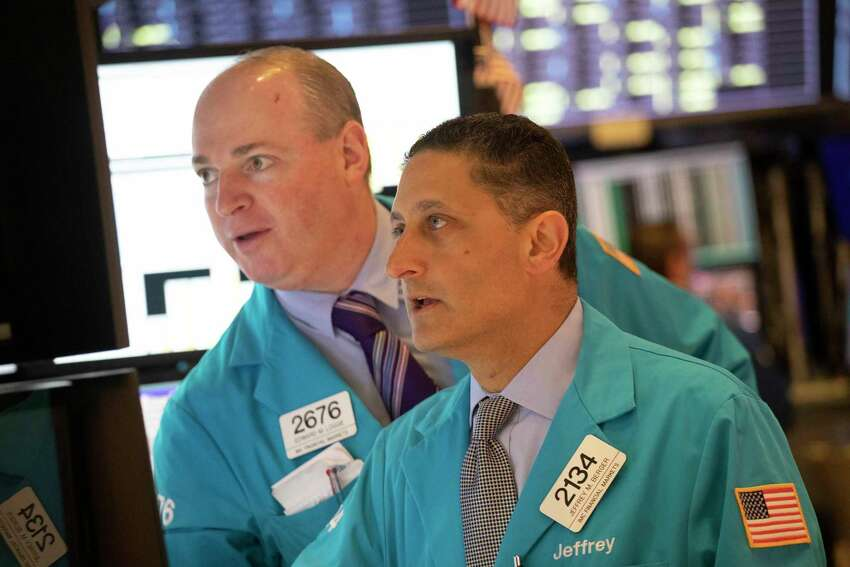 Edward Loggie, left, and Jeffrey Berger work at the New York Stock Exchange, Monday, Sept. 16, 2019. Global stock markets sank Monday after crude prices surged following an attack on Saudi Arabia's biggest oil processing facility. (AP Photo/Mark Lennihan)