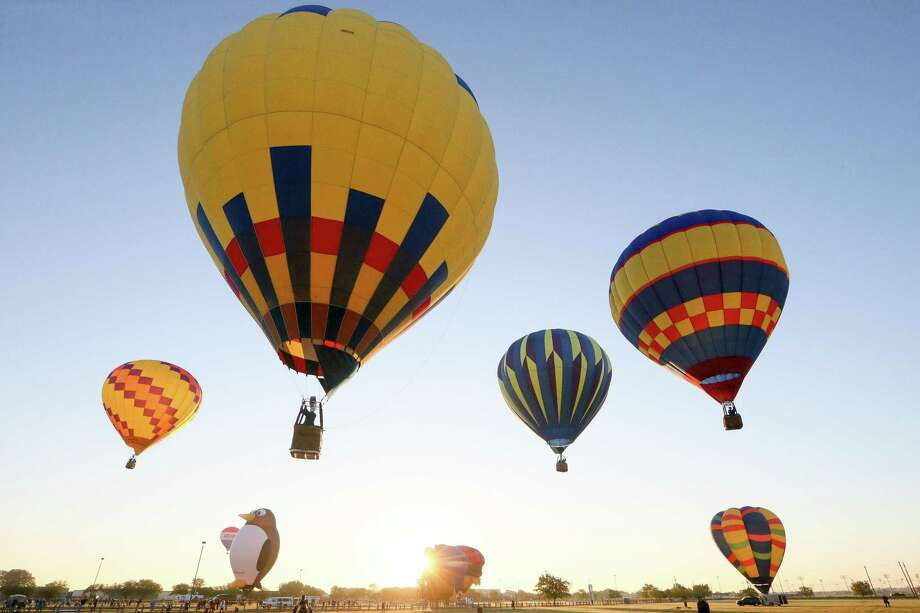 Balloons lift off at sunrise in chase of the RE/MAX balloon in the distance, in the Hare and Hound competition during the 2018 Skylight Balloon Fest on the River City Community Church grounds in Selma. This year's festival is set for Oct. 25-27. Photo: File Photo / Express-News 2018