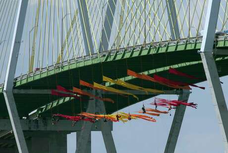 Greenpeace USA protesters dangle from the Fred Hartman Bridge Thursday, Sept. 12, 2019, in Baytown, Texas. A portion of the Houston Ship Channel has closed after about a dozen Greenpeace USA activists protesting the use of fossil fuels suspended themselves from a bridge ahead of a Democratic presidential debate.