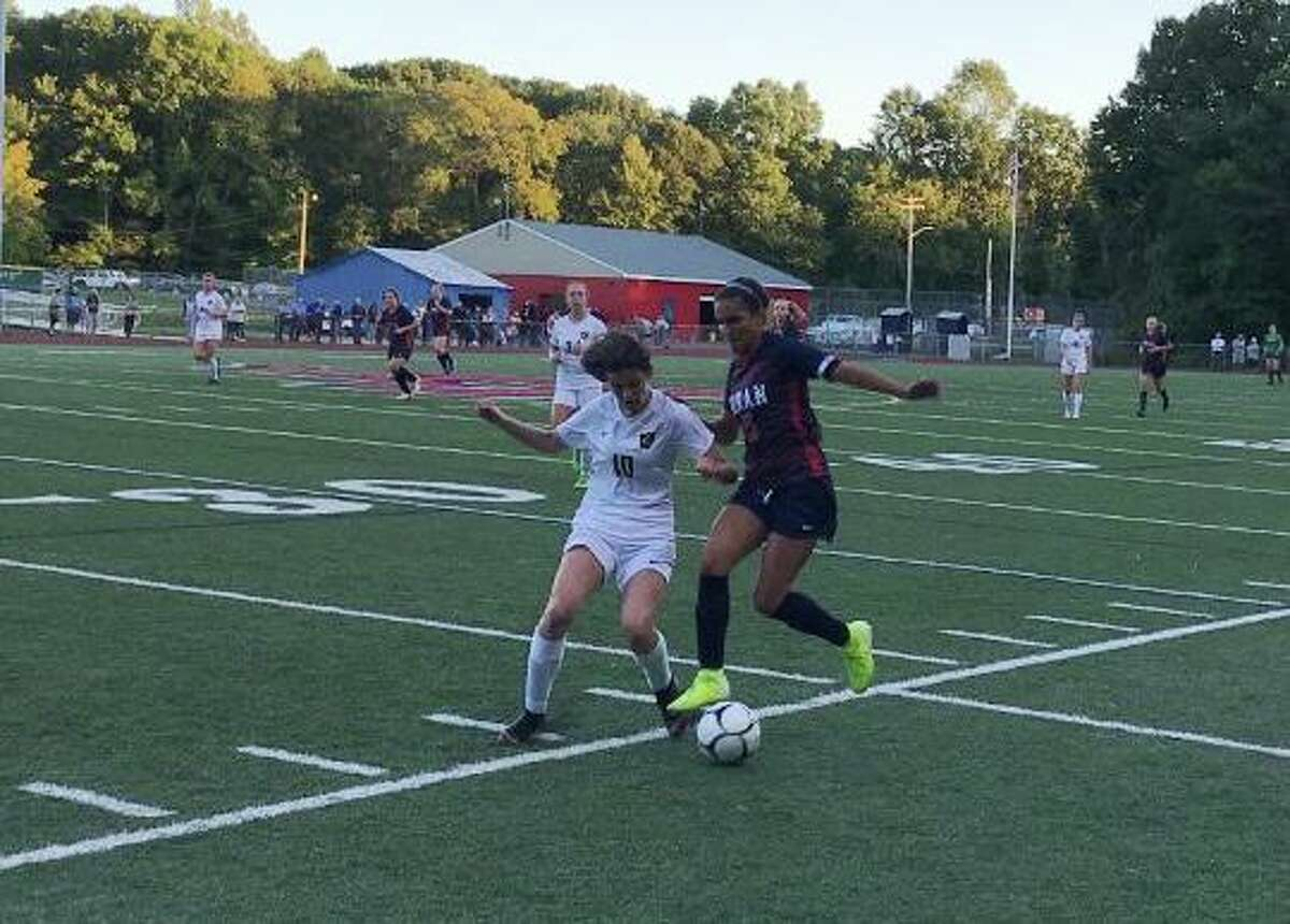 Jonathan Law's Brooke Dillman and Foran High's Ariana Montero battle for possession along the sideline.