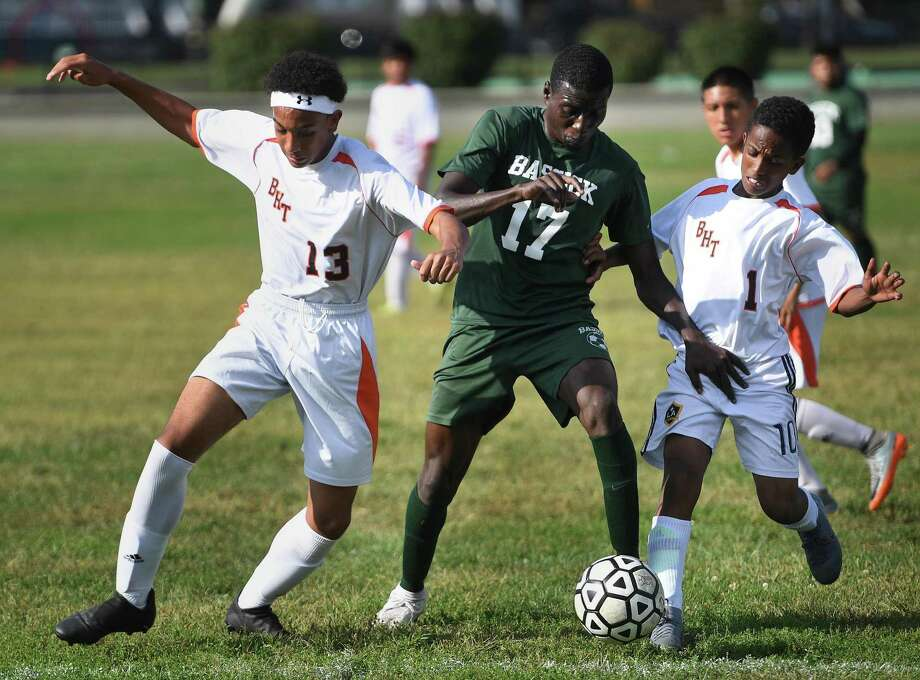 Bassick's Cleeford Cenejuste, center, works the ball between Bullard Havens defenders Raphael Briosa, left, and Gebretinsae Benhur before scoring a goal in the first half of their boys soccer matchup at Went Field in Bridgeport, Conn. on Monday, September 16, 2019. Photo: Brian Pounds / Hearst Connecticut Media / Connecticut Post