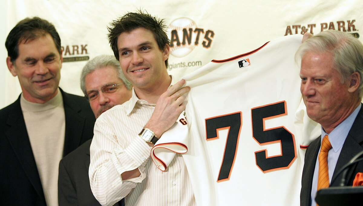Former Cy Young award winning pitcher Barry Zito (2nd R) holds up his new San Francisco Giants jersey next to Giants owner Peter Magowan (R), general manager Brian Sabean (2nd L) and manager Bruce Bochy in San Francisco, California, January 3, 2007. Zito has signed a seven-year $126 million contract with the San Francisco Giants, the biggest ever for a Major League Baseball pitcher. REUTERS/Kimberly White (UNITED STATES)