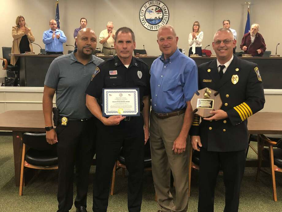 Shelton Police Officer Michael Kichar, second from left, was honored by Mayor Mark Lauretti for saving the lives of two people from their burning home in May. Pictured with Kichar are, left to right, police Chief Shawn Sequeira, Lauretti and Shelton Fire Chief Francis T. Jones III. Photo: Brian Gioiele / Hearst Connecticut Media / Connecticut Post