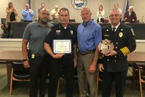 Shelton Police Officer Michael Kichar, second from left, was honored by Mayor Mark Lauretti Thursday, Sept. 12, for saving the lives of two people from their burning home in May. Pictured with Kichar are, left to right, police Chief Shawn Sequeira, Lauretti and Shelton Fire Chief Francis T. Jones III.
